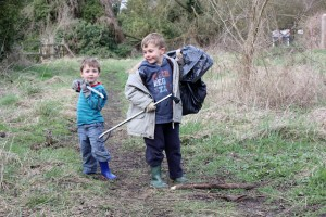 Two young boys litter picking in an open space
